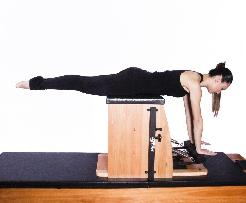 mulher em decúbito abdominal realizando exercício de pilates chair