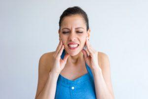 Mulher com dor que toca o maxilar