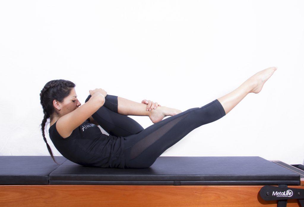 Mulher realizando exercício de pilates clássico para abdominais conhecido como The one leg stretch