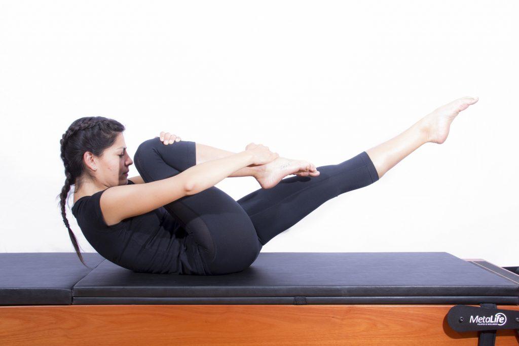 Mulher realizando exercício de pilates one leg stretch
