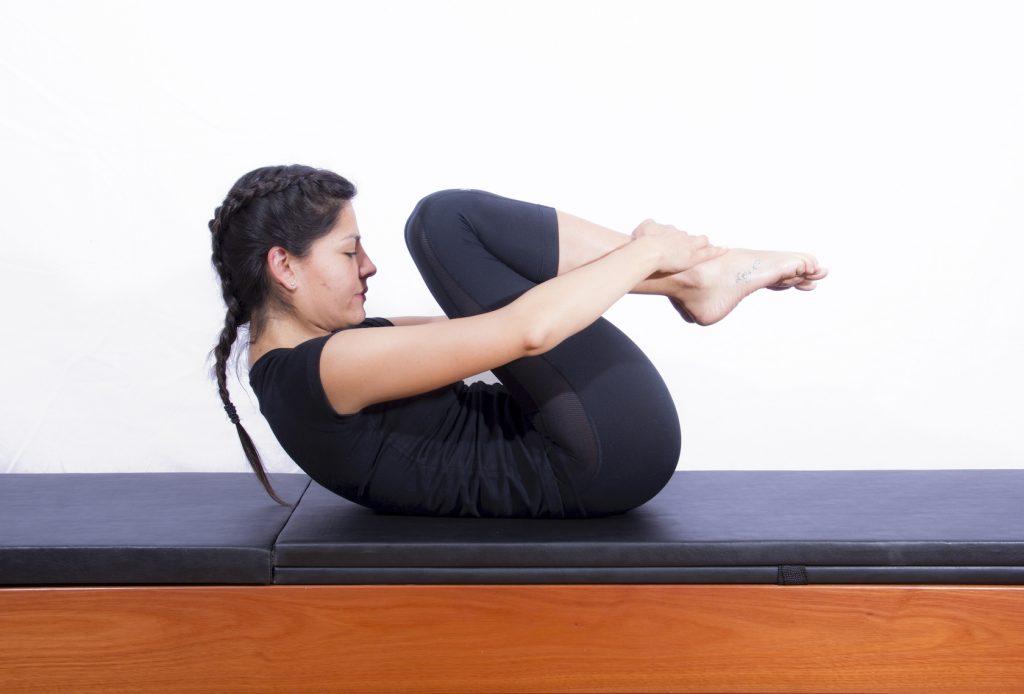 Mulher realizando exercício de pilates clássico para abdominais conhecido como double leg stretch