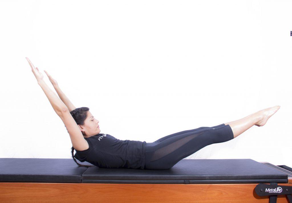 Mulher realizando exercício de pilates double leg stretch 2