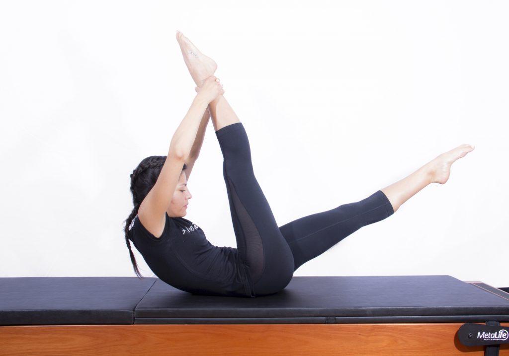 Mulher realizando exercício de pilates clássico para abdominais conhecido como the one straight leg stretch