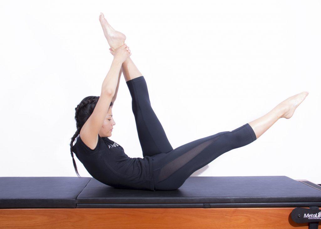 Mulher realizando exercício de pilates