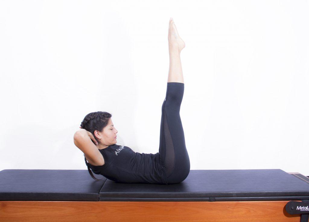 Mulher realizando exercício de pilates clássico para abdominais conhecido como the double leg stretch