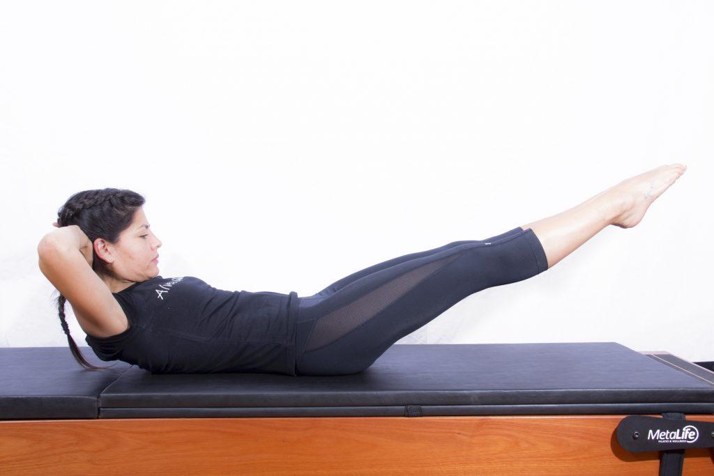 Mulher realizando exercício de pilates com pernas bem embaixo