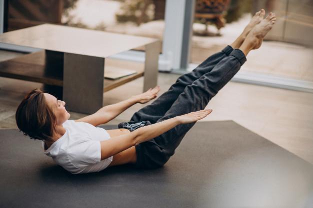 Mulher realizando exercício The Hundred de Pilates em casa