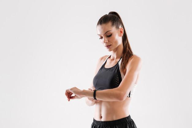 Mulher olhando o relógio para saber a hora de realizar pilates.