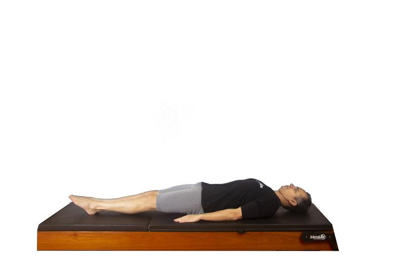 Posição inicial do exercício roll over de pilates clássico para mobilidade de coluna