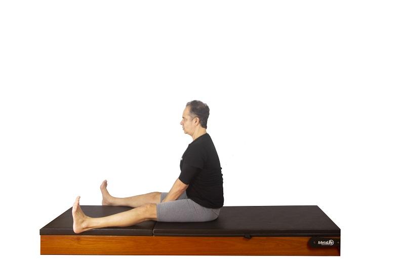 Posição inicial do exercício spine stretch de pilates clássico para mobilidade de coluna