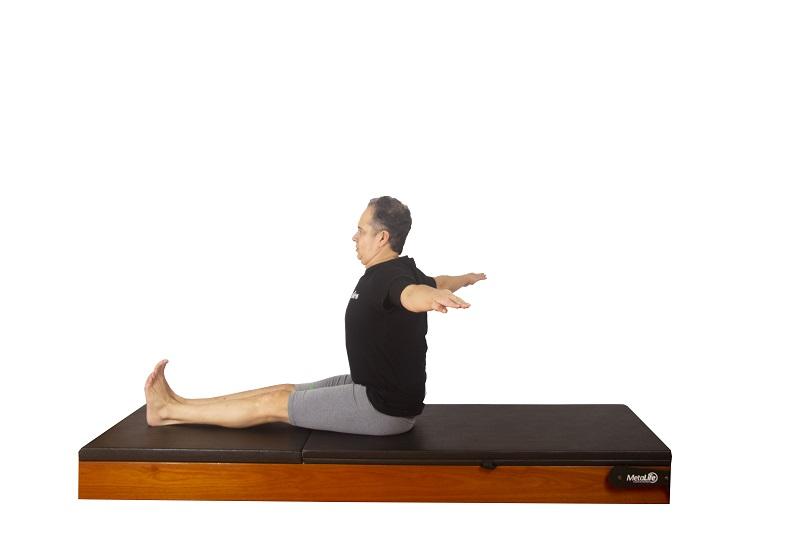 Posição inicial do exercício spine twist de pilates clássico para mobilidade de coluna