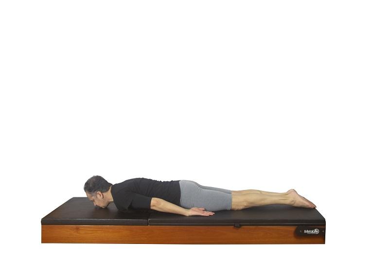 Posição inicial do exercício rocking de pilates clássico para mobilidade de coluna