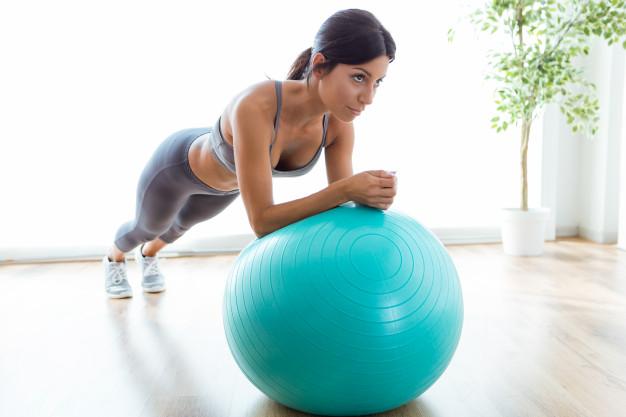 Mulher realizando exercício de pilates com bola para hérnia de disco
