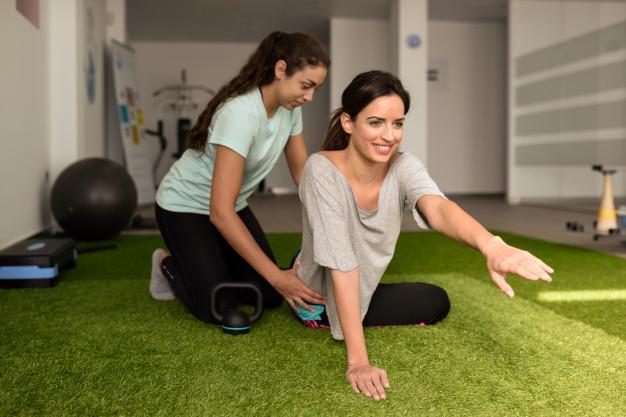 Fisioterapeuta tratando patologias da aluna com pilates