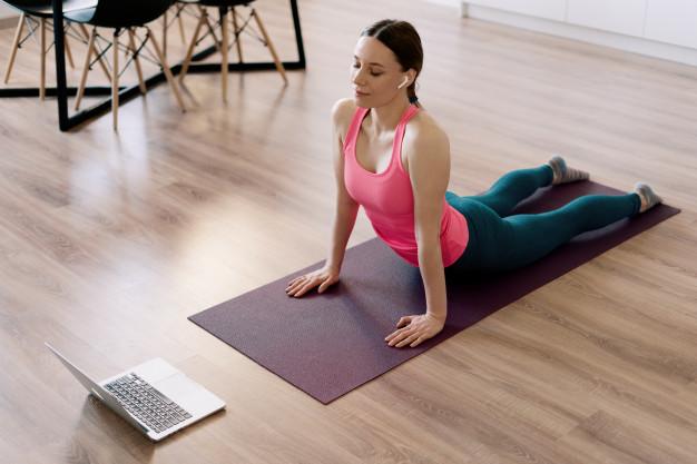 Mulher realizando exercício swan na aula de pilates online